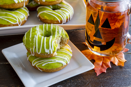 jack o lantern: Plate of homemade baked caramel apple donuts with green apple glaze with bite out of top donut sitting on white plate with jack o lantern mason jar mug filled with orange drink