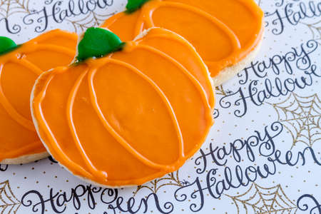 frosted: 3 homemade frosted pumpkin sugar cookies on Happy Halloween background