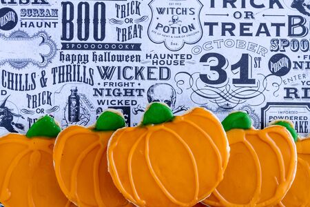 frosted: Homemade frosted pumpkin sugar cookies stacked on Halloween graphics background