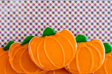 Homemade frosted pumpkin sugar cookies stacked on grunge autumn colored checkered background