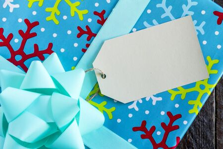 wrapped present: Christmas present wrapped in bright blue wrapping paper with colorful snowflakes with blue bow and blank tag sitting on wooden table Stock Photo