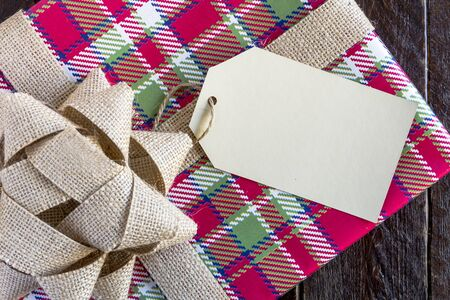 Christmas present wrapped in colorful plaid wrapping paper with brown burlap bow and blank tag sitting on wooden table