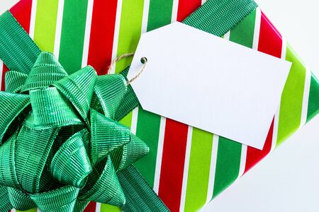 tag: Christmas present wrapped in red and green striped wrapping paper with shiny green bow and blank tag sitting on white background