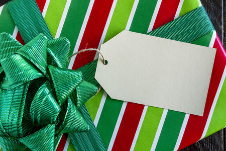 Christmas present wrapped in red and green striped wrapping paper with shiny green bow and blank tag sitting on wooden table