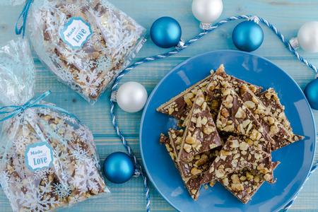 cioccolato natale: biscotti frollini fatti in casa ricoperti di cioccolato e noci seduto sul piatto blu con decorazioni di festa e confezioni regalo alimentari