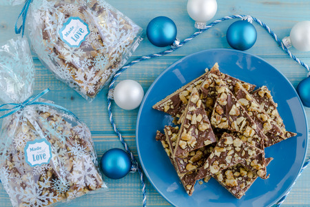 traditional gifts: Homemade shortbread cookies coated with chocolate and walnuts sitting on blue plate with holiday decorations and food gift packages