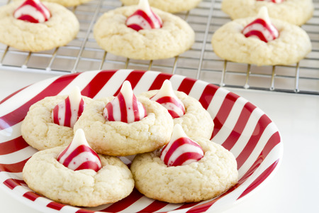 kiss biscuits: Fresh baked candy cane white chocolate cookies siting on red and white striped plate on white background in front of wire baking rack filled with cookies Stock Photo