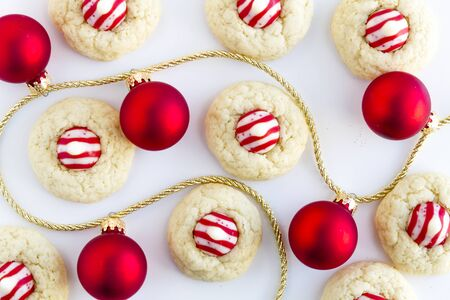 kiss biscuits: Homemade candy cane white chocolate cookies siting on white background surrounded by red ornaments on gold string Stock Photo