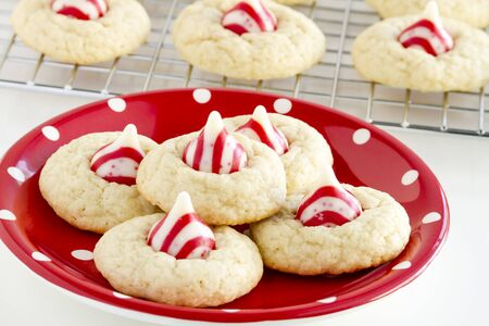 kiss biscuits: Fresh baked candy cane white chocolate cookies siting on red and white polka dot plate on white background in front of wire baking rack filled with cookies Stock Photo
