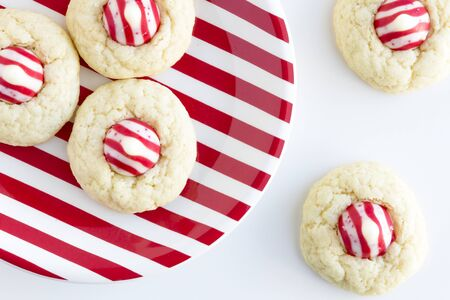 kiss biscuits: Homemade candy cane white chocolate cookies siting on red and white striped plate on white background shot from above Stock Photo