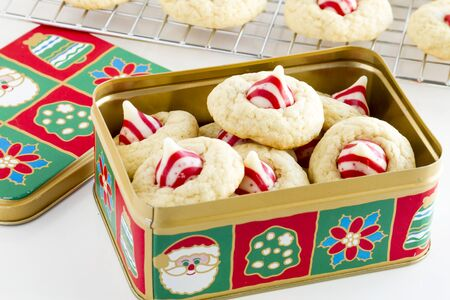 kiss biscuits: Homemade candy cane white chocolate cookies in Christmas holiday cookie tin in front of wire baking rack filled with cookies