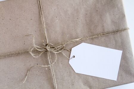 tied in: Christmas present wrapped in brown wrapping paper with brown burlap twine tied in a bow and blank tag sitting on white background