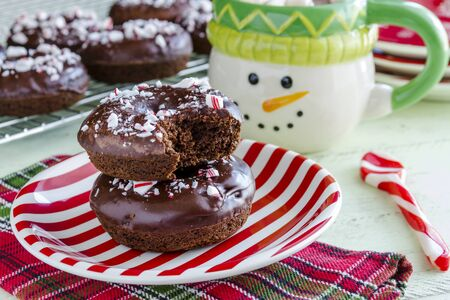 hot cocoa: Christmas breakfast table with double chocolate peppermint donuts sitting on red and white striped plate with hot cocoa in snowman mug