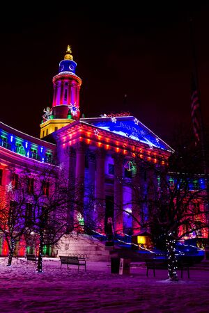 denver city and county building: Denver Colorado historic City and County building in Civic Center Park decorated with holiday lights on snowy winter evening