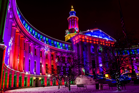 christmas in denver: Denver Colorado historic City and County building in Civic Center Park decorated with holiday lights on snowy winter evening