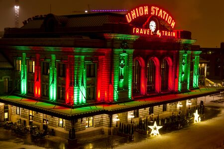 denver at christmas: Historic landmark Union Station in downtown Denver Colorado decorated with holiday lights on snowy winter night