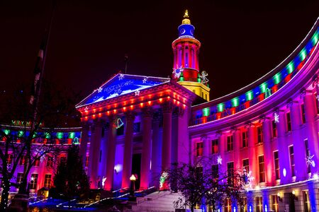 Denver Colorado historic City and County building in Civic Center Park decorated with holiday lights on snowy winter evening