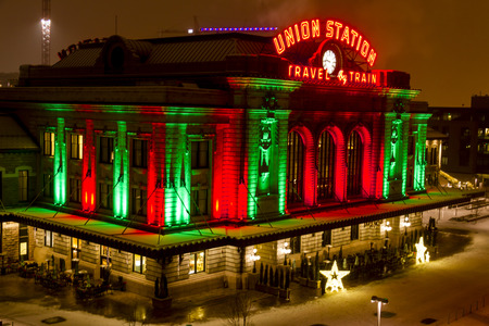 christmas in denver: Historic landmark Union Station in downtown Denver Colorado decorated with holiday lights on snowy winter night