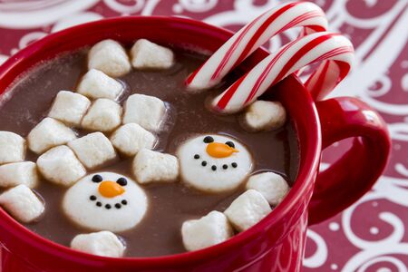 peppermint candy: Red mug filled with hot chocolate with snowman shaped marshmallows, peppermint candy canes on red swirled background