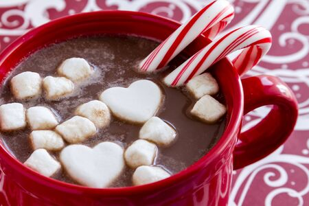 peppermint candy: Red mug filled with hot chocolate with heart shaped marshmallows, peppermint candy canes on red swirled background Stock Photo
