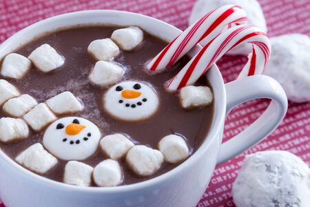 peppermint candy: White mug filled with hot chocolate with snowman shaped marshmallows, peppermint candy canes and snowball cookies on red Merry Christmas background