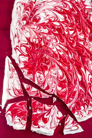 swirled: White chocolate peppermint red swirled candy bark sitting on red background
