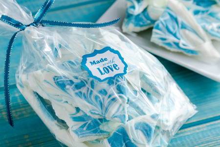 swirled: Pieces of white chocolate vanilla blue swirled candy bark wrapped in clear wrapper tied with blue ribbon and made with love sticker on front
