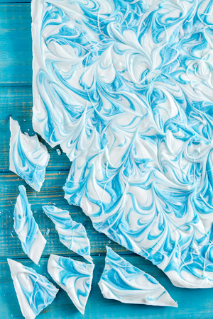 swirled: White chocolate vanilla blue swirled candy bark sitting on blue background Stock Photo