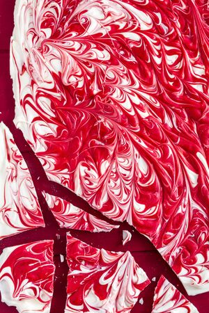 swirled: Close up of white chocolate peppermint red swirled candy bark sitting on red background Stock Photo