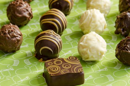 chocolate truffles: Rows of assorted chocolate truffles sitting on green Christmas background Stock Photo