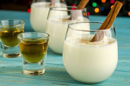 egg nog: Close up of row of small glasses filled with homemade egg nog with cinnamon sticks alongside shots of dark rum on blue wooden table with Christmas tree lights in background