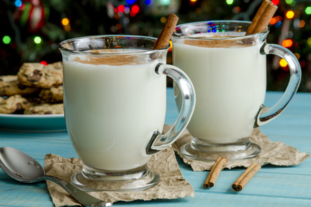egg nog: Glass mugs filled with homemade egg nog with cinnamon sticks and chocolate chip cookies on blue wooden table and Christmas tree lights in background