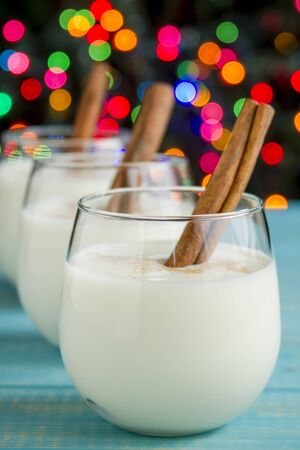 egg nog: Row of small glasses filled with homemade egg nog with cinnamon sticks on blue wooden table with Christmas tree lights in background Stock Photo