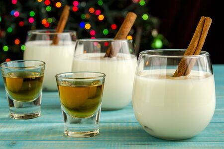 egg nog: Row of small glasses filled with homemade egg nog with cinnamon sticks alongside shots of dark rum on blue wooden table with Christmas tree lights in background Stock Photo