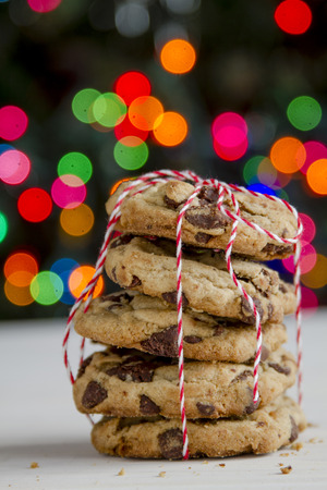 christmas baker's: Stack of homemade chocolate chip cookies wrapped in red and white bakers twine with Christmas tree lights in background