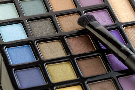 nudes: Close up of cosmetic brush sitting on bright colorful palette of shimmering eye shadow colors