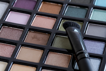 Close up of cosmetic brush sitting on bright colorful palette of shimmering eye shadow colors
