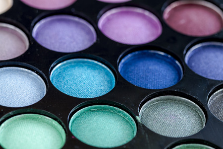 purples: Close up of colorful palette of eye shadows in blues, greens and purples Stock Photo