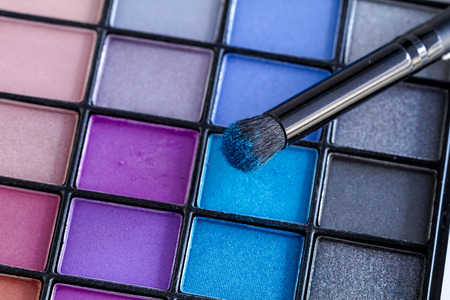 nudes: Cosmetic brush with bright blue eye shadow dust sitting on top of palette of blues and purples eye shadow shades