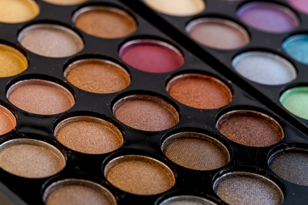 browns: Close up of colorful palette of eye shadows in browns, golds and yellows