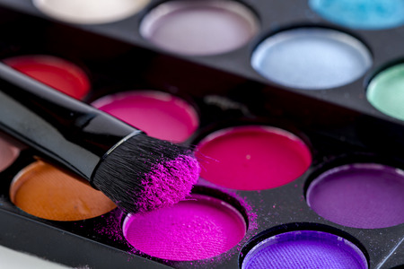 nudes: Close up of cosmetic brush with hot pink eye shadow dust sitting on top of colorful palette of eye shadows