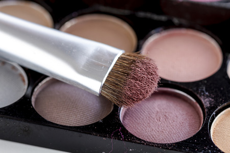 nudes: Close up of cosmetic brush with mauve eye shadow dust sitting on top of palette of nude eye shadow shades