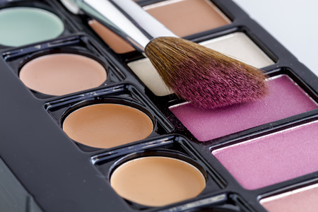 Large cosmetic brush with pink blush dust sitting on palette of blush and skin cover up colors Stock Photo
