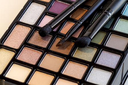 Colorful palette of eye shadows in a variety of shimmering colors with three cosmetic brushes