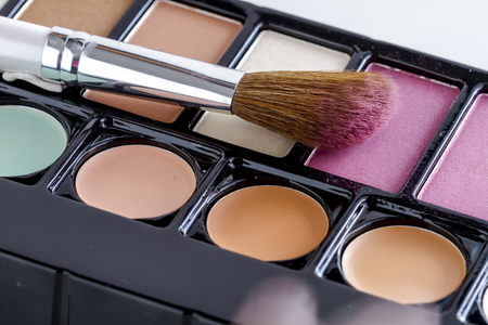 nudes: Large cosmetic brush with pink blush dust sitting on palette of blush and skin cover up colors Stock Photo