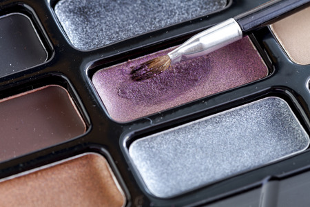 nudes: Close up of cosmetic lip brush with purple lipstick sitting on palette of lip colors