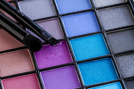brightly colored: Two cosmetic brush with purple shimmering eye shadow dust sitting on top of palette of brightly colored eye shadow shades