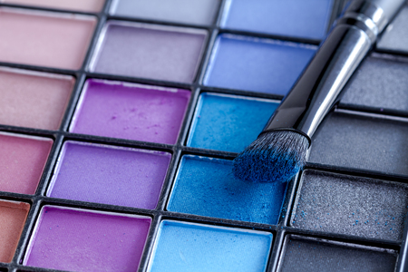 purples: Cosmetic brush with bright blue eye shadow dust sitting on top of palette of blues and purples eye shadow shades