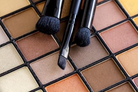 browns: Three cosmetic brushes sitting on top of colorful palette of nude eye shadow colors