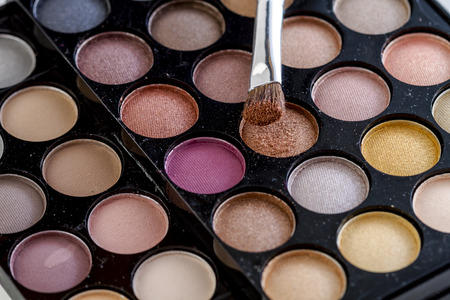 Close up of cosmetic brush with brown shimmering eye shadow dust sitting on top of palette of nude eye shadow shades